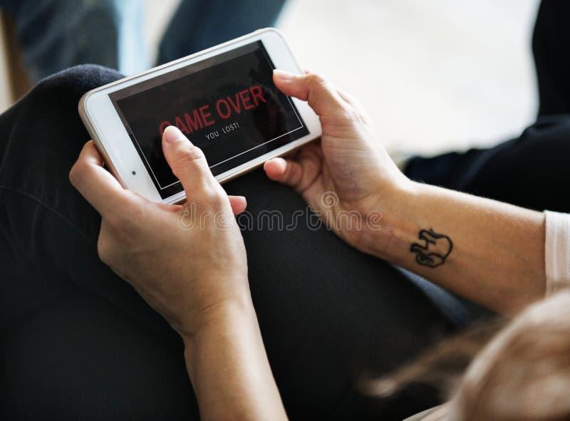 Closeup av folk som spelar online spelet på mobiltelefonen royaltyfria bilder