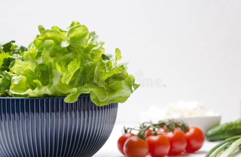 Closeup av grönsallatsidor i bunken och de olika ingredienserna för att laga mat Nya och läckra grönsaker som förbereds för att l royaltyfri foto