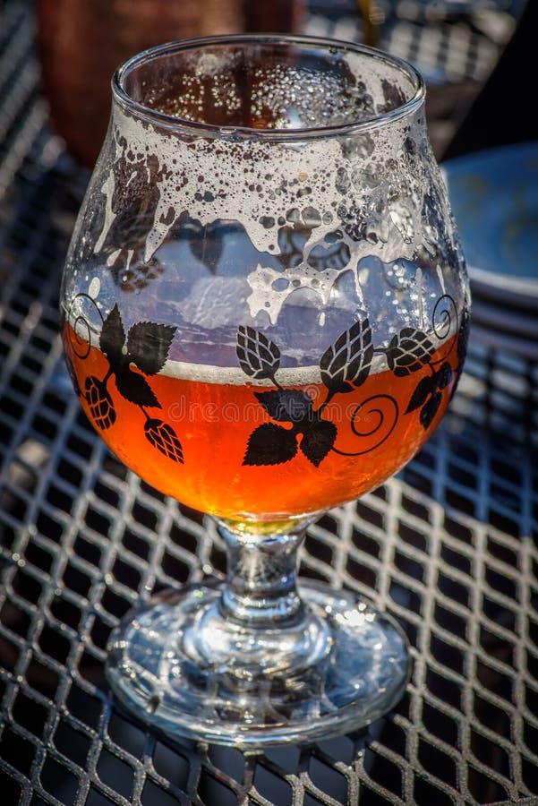 Closeup av guld- exponeringsglas av öl arkivfoto