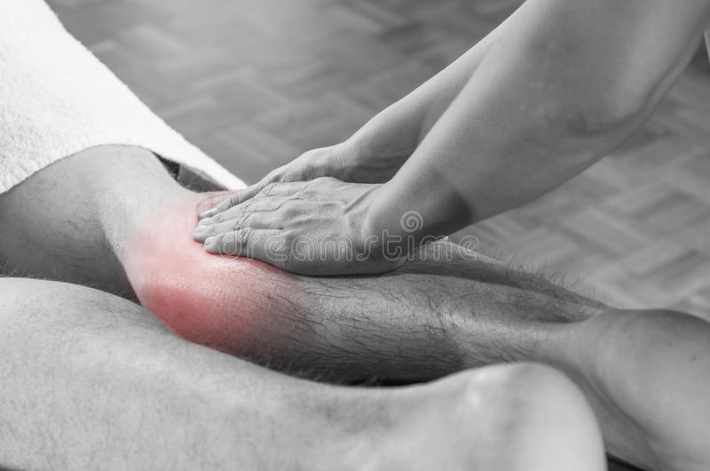 Closeup av händer av kiropraktorn/fysioterapeuten som gör kalvmusc arkivfoto