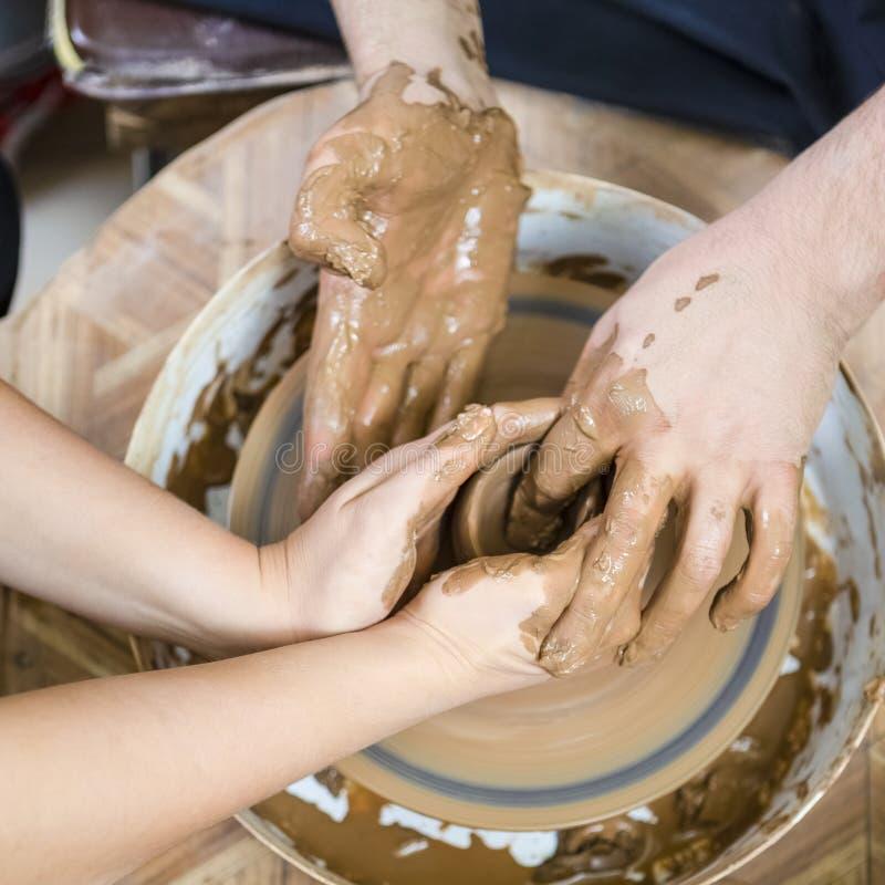 Closeup av händer av den erfarna manliga keramikern som arbetar med den kvinnliga lärlingen Arbeta med Clay Lump på keramikers hj royaltyfri bild