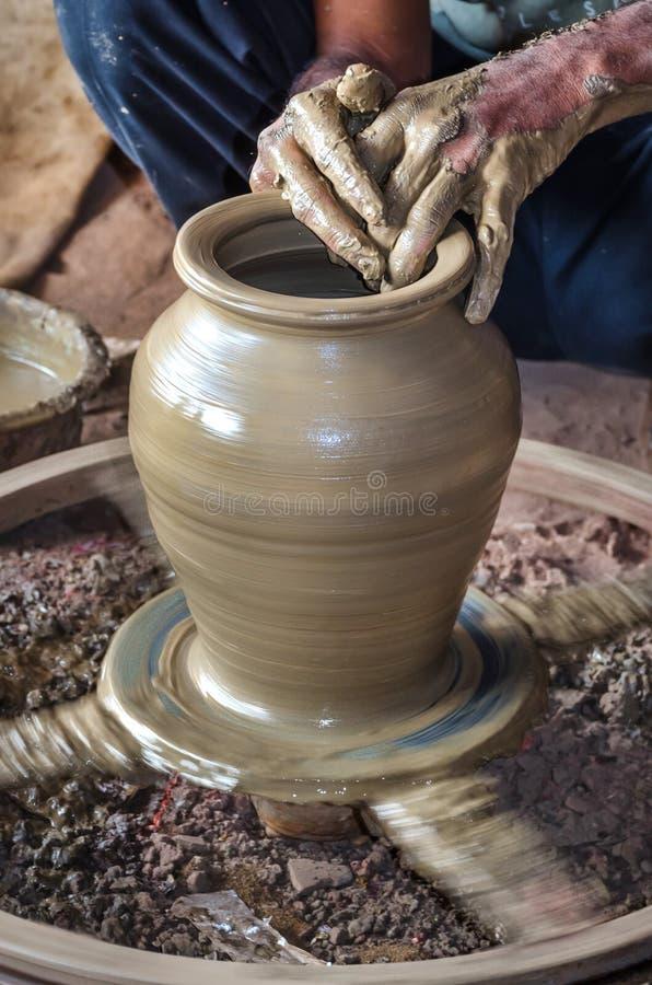 Closeup av händer för keramiker` som s gör lera att bevattna krukan på krukmakerihjulet royaltyfri foto
