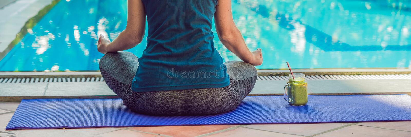 Closeup av händer för kvinna` ett s under meditation med gröna smoothies av spenat, apelsinen och bananen på bakgrunden av pölen  fotografering för bildbyråer