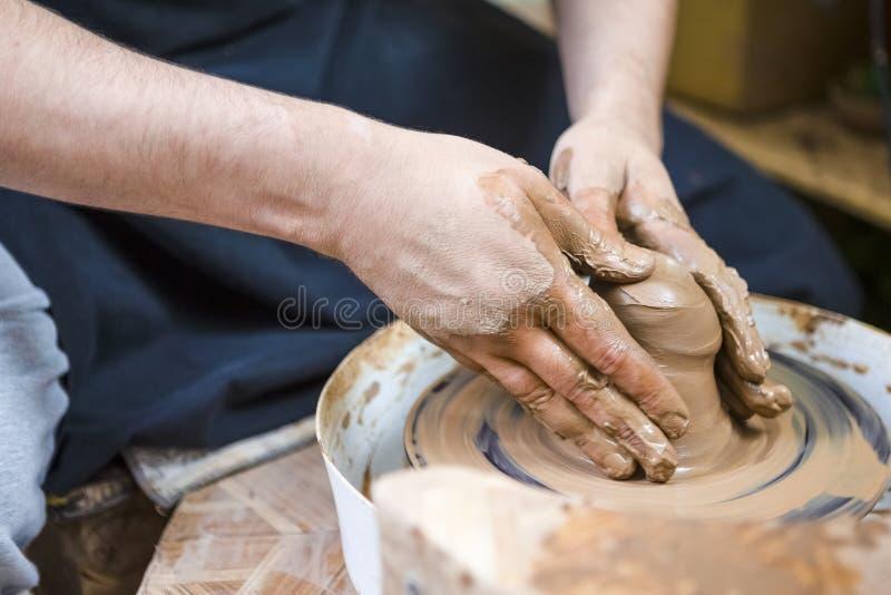 Closeup av händer av manligt keramikerarbete med Clay Lump på keramikers för hjul seminarium in arkivfoto