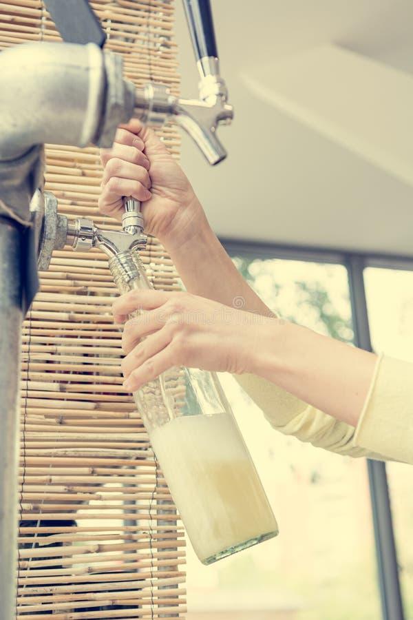 Closeup av händer som häller organisk fruktsaft från ett klapp in i glasflaskan royaltyfria foton
