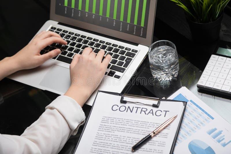 Closeup av händer som skriver på bärbara datorn som ligger bredvid avtal royaltyfri foto