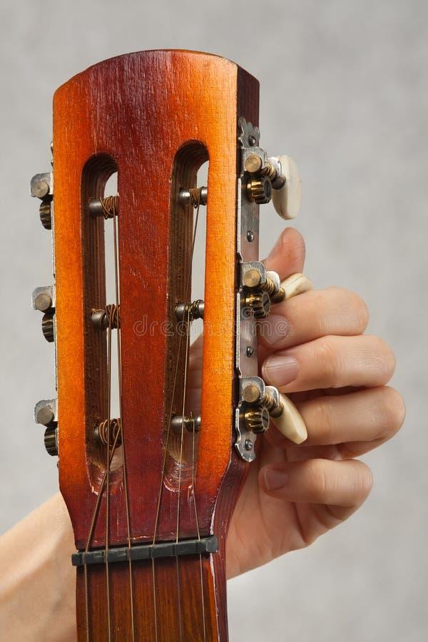 Closeup av händer som trimmar den akustiska gitarren arkivbilder