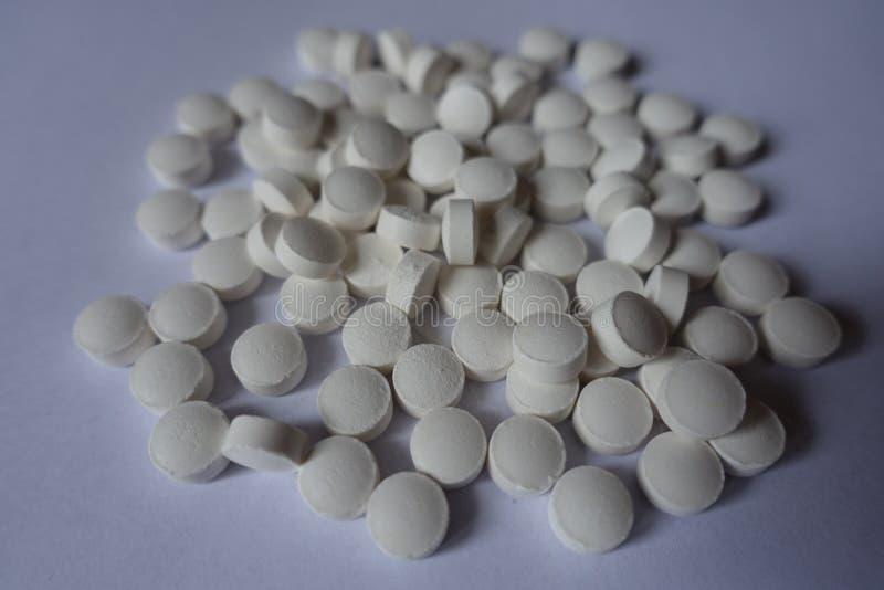 Closeup av högen av vita minnestavlor av vitaminet K2 arkivbild