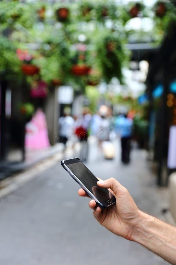 Closeup av handen genom att använda smartphonen i stadsgata royaltyfria bilder