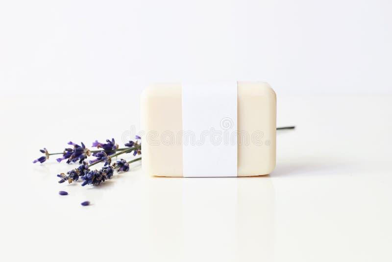 Closeup av handen - gjord växt- packe för etikett för papper för tvålstångblanko och grupp av lavendelblommor på vit tabellbackro royaltyfri bild