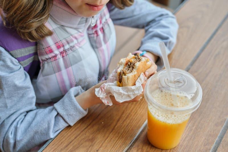 Closeup av handen av ungen som äter hamburgaren och dricker orange fruktsaft royaltyfri fotografi