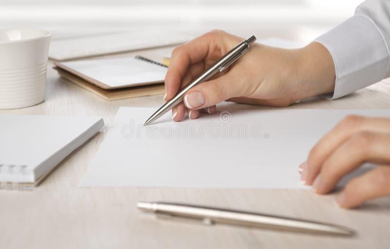 Closeup av handstil för hand för affärskvinna på papper på skrivbordet royaltyfria bilder