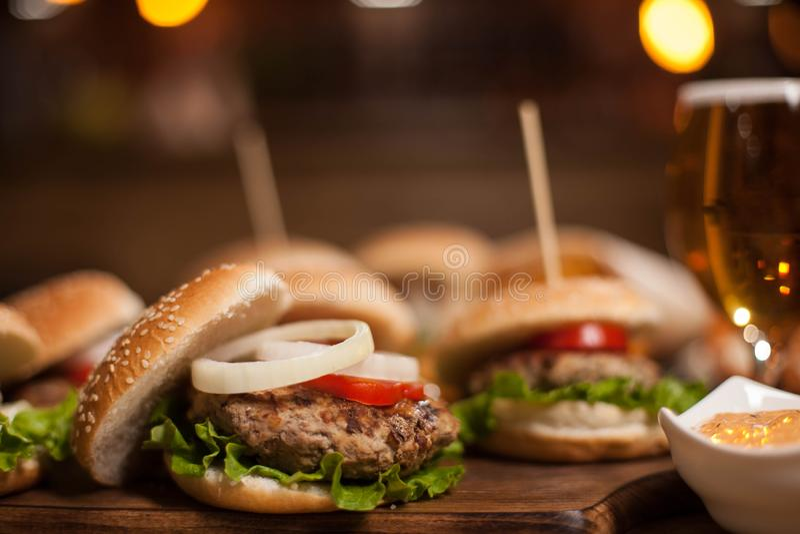Closeup av hemlagade hamburgare på träskärbräda royaltyfri fotografi