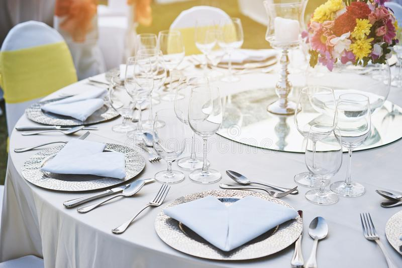 Closeup av inställningen för tabell för matställe för bröllopmottagande med vattenexponeringsglas, servetten, plattan, skeden och arkivbilder