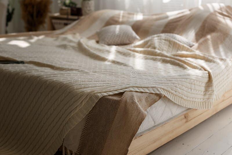 Closeup av komfortdubbelsäng med beigea kuddar och filten, solstrålar och skuggor i hemtrevligt sovrum fotografering för bildbyråer