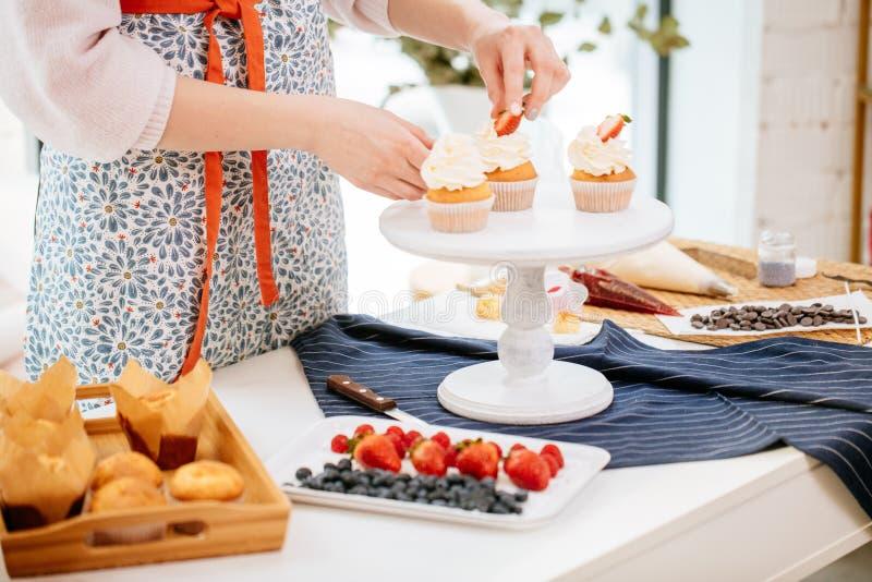 Closeup av konditor som dekorerar muffin med bär royaltyfria bilder