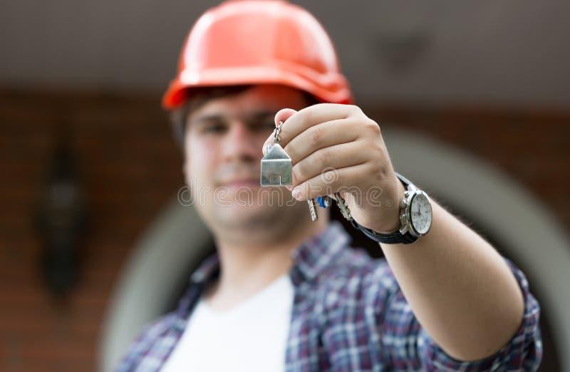 Closeup av konstruktionsteknikern som ger tangenter från nytt hus royaltyfria bilder