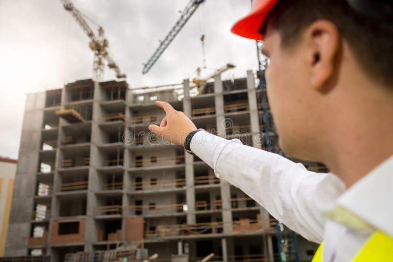 Closeup av konstruktionsteknikern som pekar med handen på byggnad arkivfoton