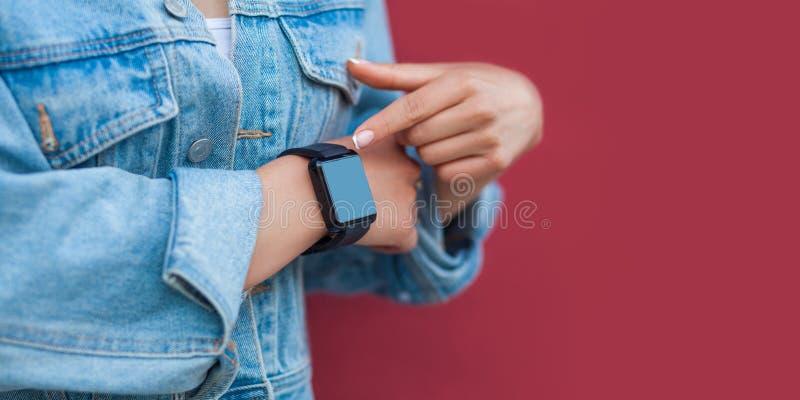 Closeup av kvinnahänder i tillfällig stil med den svarta smarta klockan som pekar eller trycker på och att avskärma copyspace arkivfoton