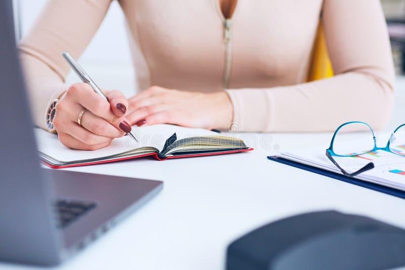 Closeup av kvinnahanden med penntecknet på papperet Slutet av en affärskvinna räcker upp handstil i ett dokument på ett skrivbord royaltyfri fotografi