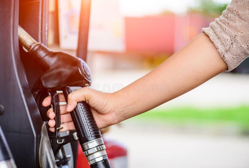 Closeup av kvinnahanden som rymmer en bränslepump på en station royaltyfri fotografi