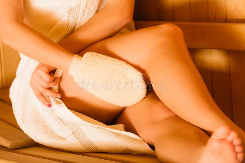 Closeup av kvinnan i bastu med den exfoliating handsken fotografering för bildbyråer