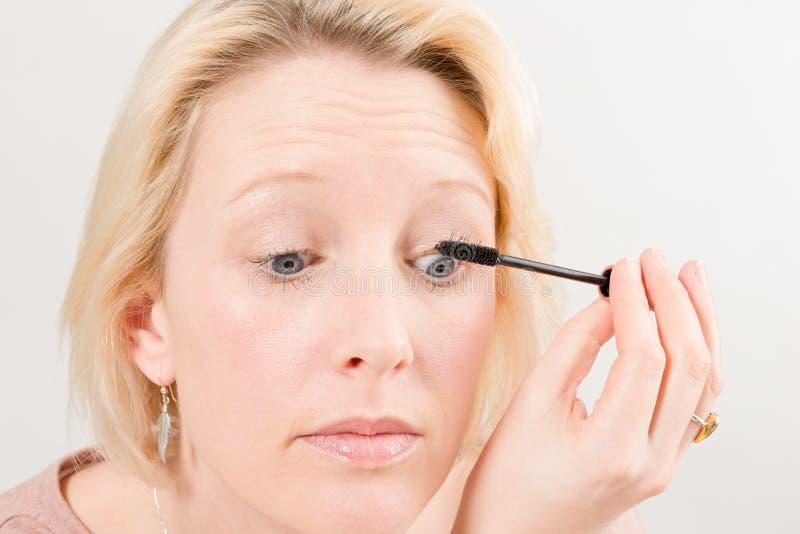 Closeup av kvinnan som applicerar mascarasmink arkivbild
