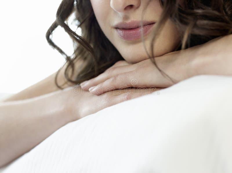 Closeup av kvinnan som vilar huvudet på knäppte fast händer arkivfoton