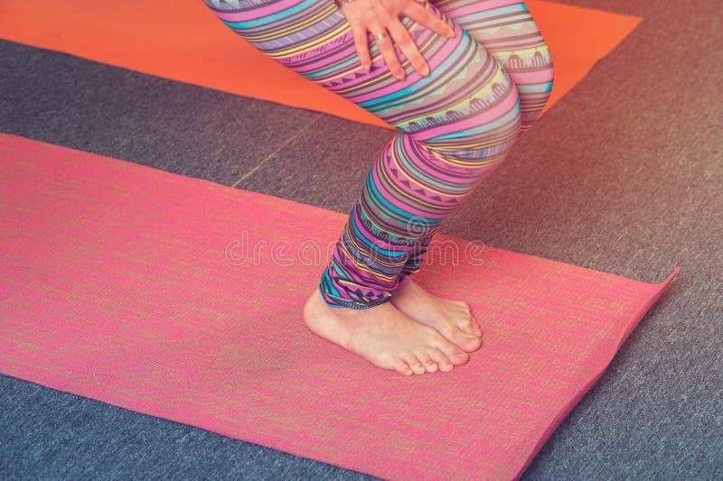 Closeup av kvinnlig vuxen praktiserande yoga på mattt royaltyfria foton