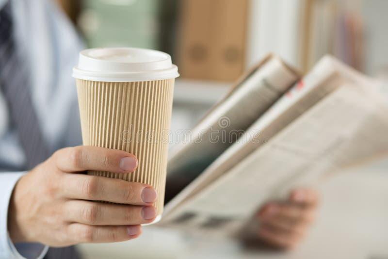 Closeup av läs- nyheterna för affärsman och den hållande kaffekoppen royaltyfria bilder