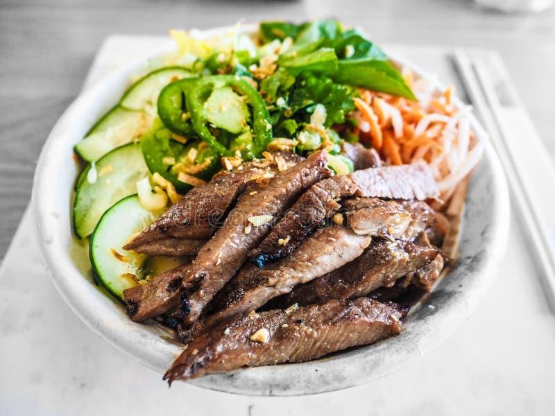 Closeup av lagat mat nötkött med skivade grönsaker i en vit bunke arkivbild