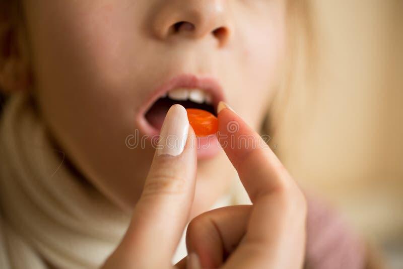 Closeup av lilla flickan som tar medicin i preventivpiller royaltyfri fotografi