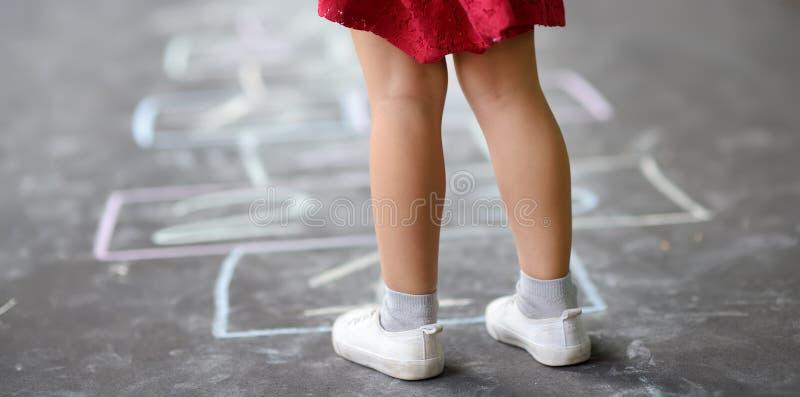 Closeup av liten flickas ben och hoppa hage som dras på asfalt Barn som hoppar hage leken p? lekplats utomhus p? en solig dag arkivbild