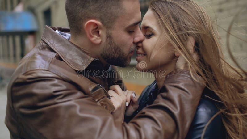 Closeup av lyckliga älska par som kysser och omfamnar, medan havinhg går i stadsgata royaltyfria bilder
