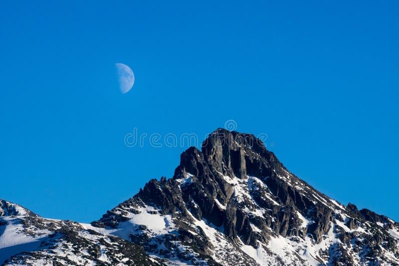 Closeup av månen som stiger över bergmaximumet royaltyfri foto