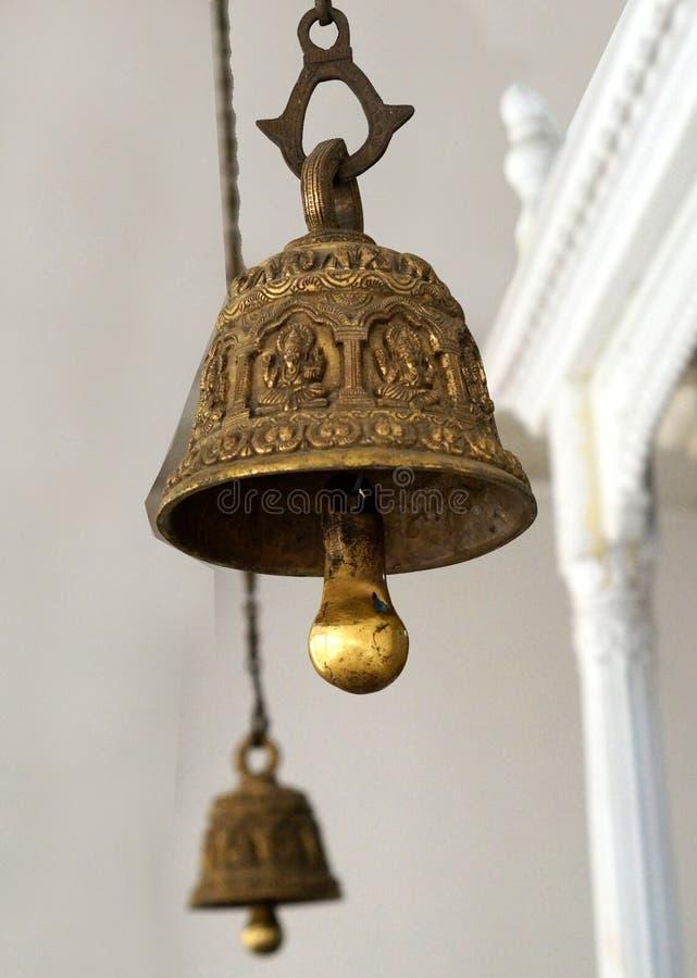 Closeup av m?ssingsklockan som framme h?ngs av gud i hinduisk tempel arkivfoton