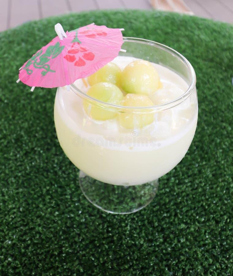 Closeup av malonfruktsaft i vitt exponeringsglas på tabellen royaltyfri fotografi