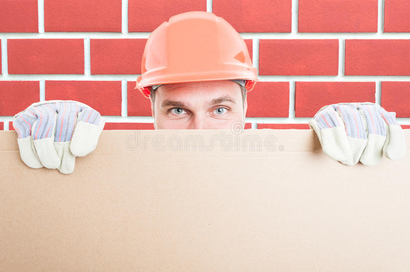 Closeup av manbyggmästaren som rymmer det stora plakatet fotografering för bildbyråer