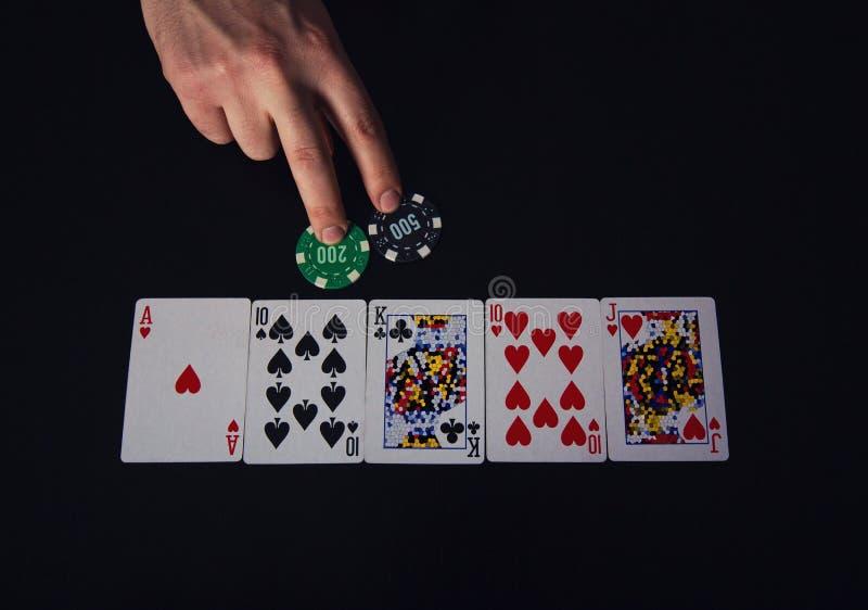 Closeup av manhanden, pokerspelare som bluffar, som slå vad två chiper Spela på kasinodobbeltabellen, okänd kortkombination royaltyfri fotografi