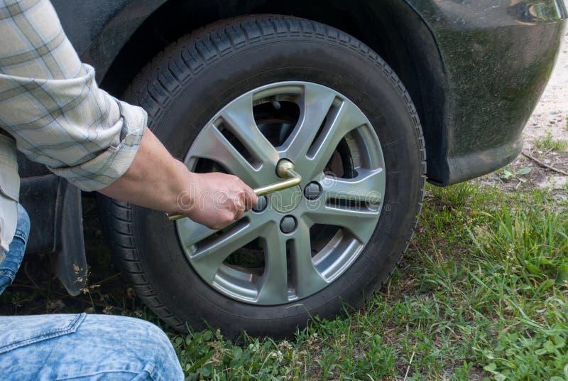 Closeup av manliga händer genom att använda en skiftnyckel för ett bilgummihjul Hjulutbyte efter en olycka i en solig dag Showbil arkivbild