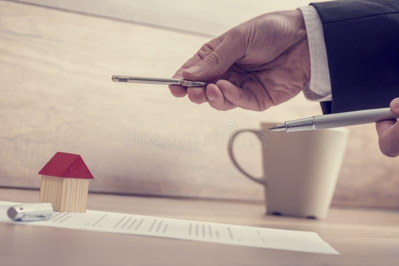 Closeup av manliga händer som rymmer en hustangent och en penna över en contr arkivbild