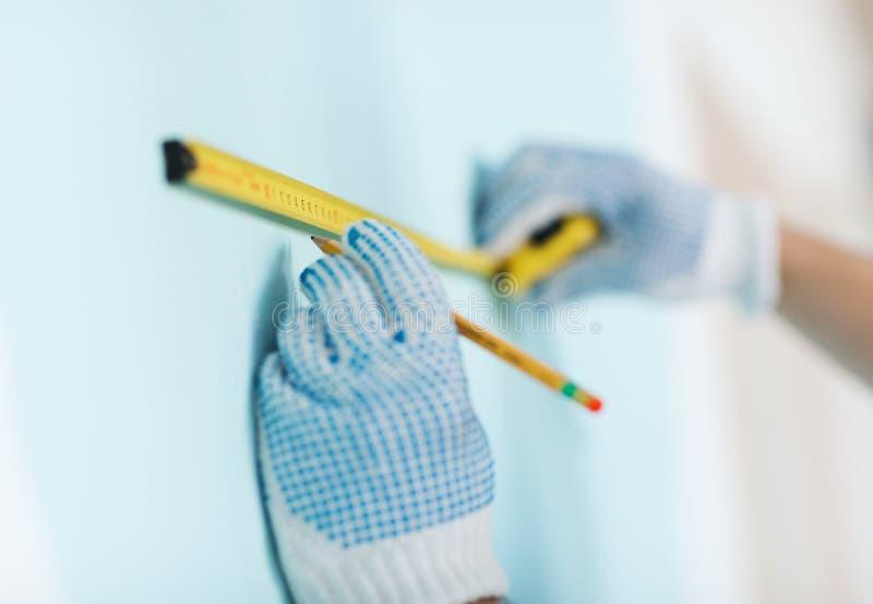 Closeup av mannen i handskar som mäter väggen med bandet arkivbilder