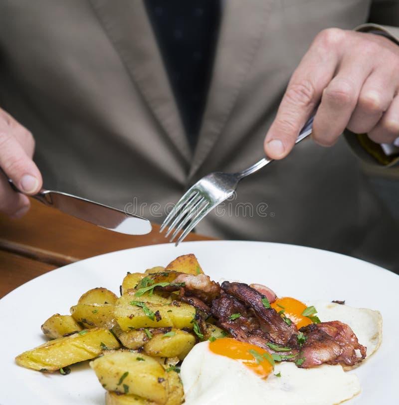 Closeup av mannen som äter stekt ägg, potatisar och bacon royaltyfri foto