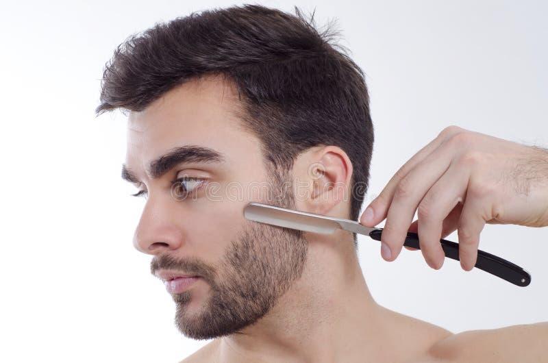 Closeup av mannen som rakar med den skarpa rakkniven royaltyfria foton