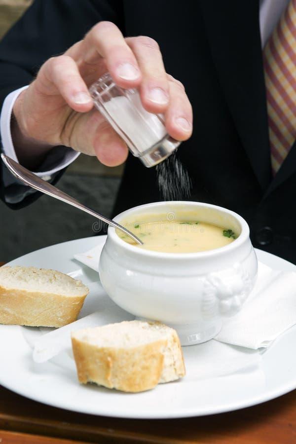 Closeup av mannen som sätter som är salt i en bunke av soppa royaltyfri fotografi