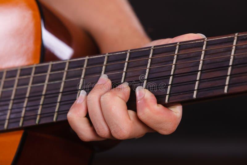 Closeup av mannen som spelar den akustiska gitarren arkivbild