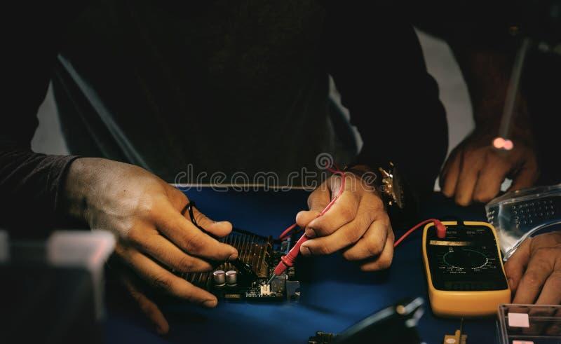 Closeup av multimeteren som mäter datorströmkretsbrädet fotografering för bildbyråer