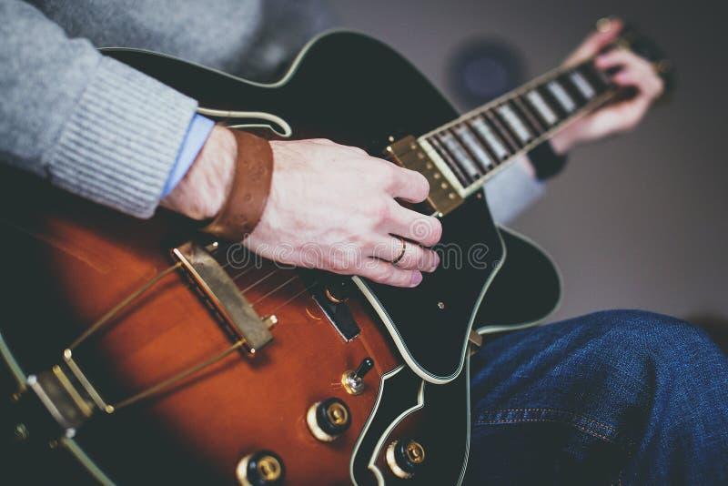 Closeup av musikern med händer på gitarren arkivbilder