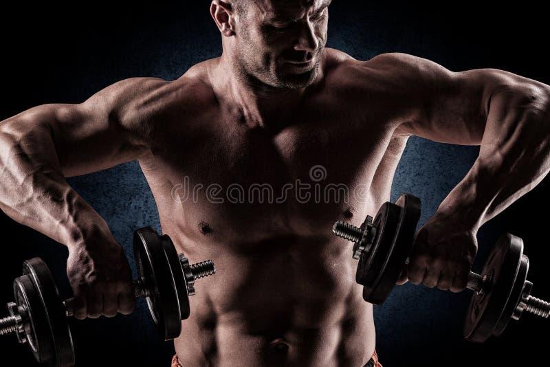 Closeup av muskulösa lyftande vikter för en ung man på mörk backgrou royaltyfria bilder