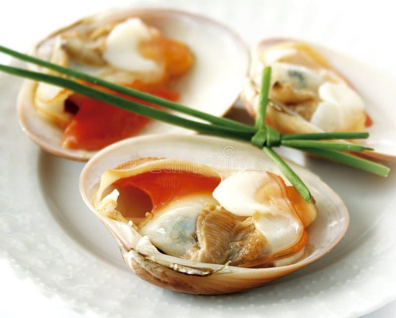 Closeup av musslor som garneras med gräslökar arkivfoton